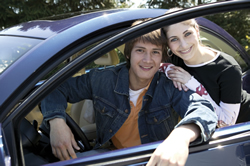 Teen boy and girl with a car
