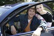 photo: boy and girl by a car