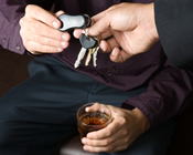 photo: man holding a drink handing over his keys