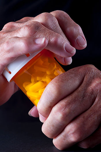 Hands securing a medication bottle lid