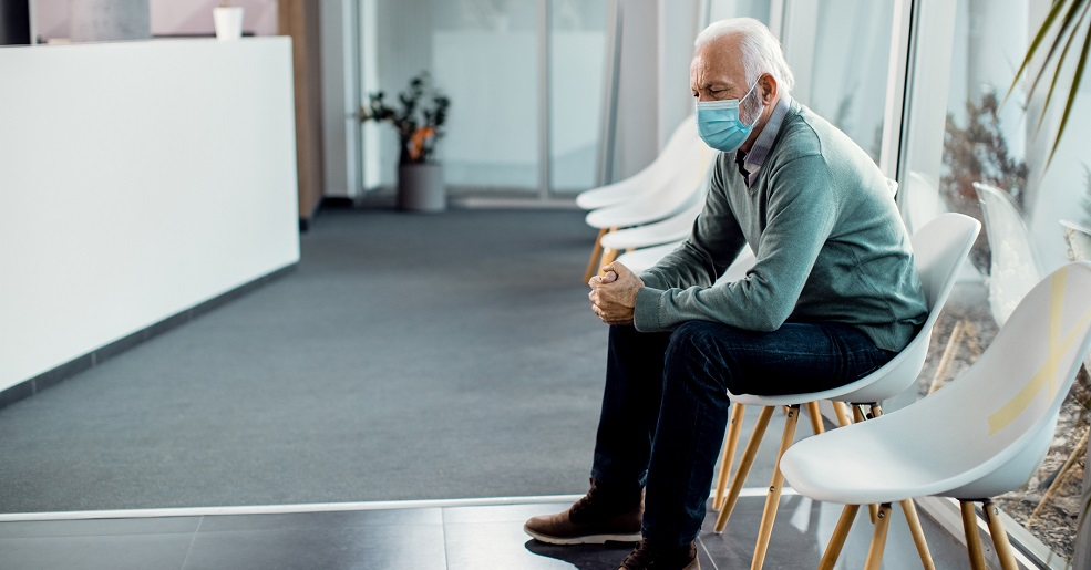 Pensive senior man with protective face mask sitting in waiting room