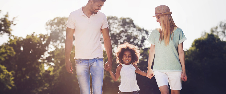 father with wife and young daughter walking through field smiling