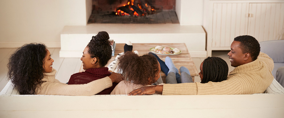 family sitting on couch in front of fireplace