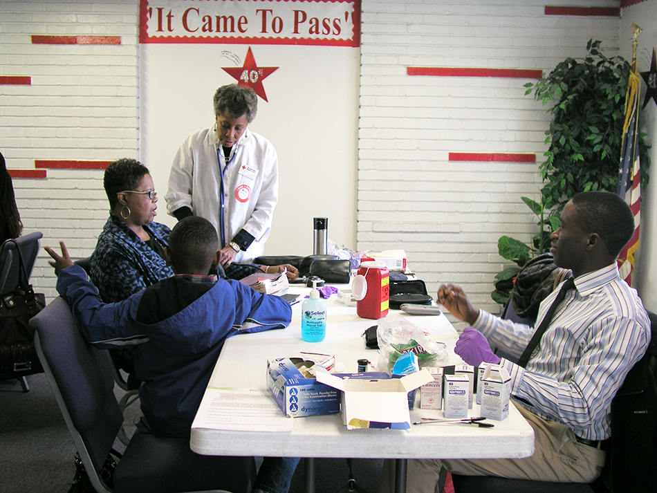 A volunteer nurse provides health information to a Body and Soul Program participant at a church kick-off event.