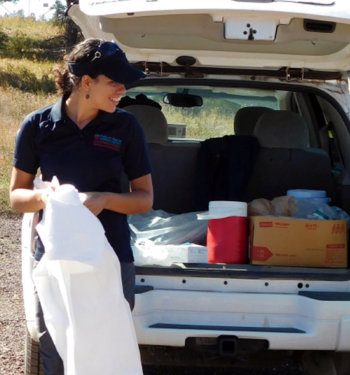 Helena Archer preparing supplies near a vehicle's hatchback