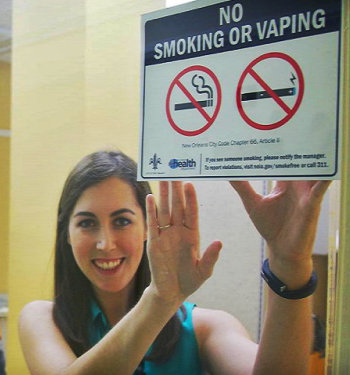 Photo of Allison Napier posting a sign to a window that reads No Smoking or Vaping