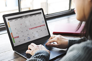 Lady sitting with laptop looking at monthly calendar
