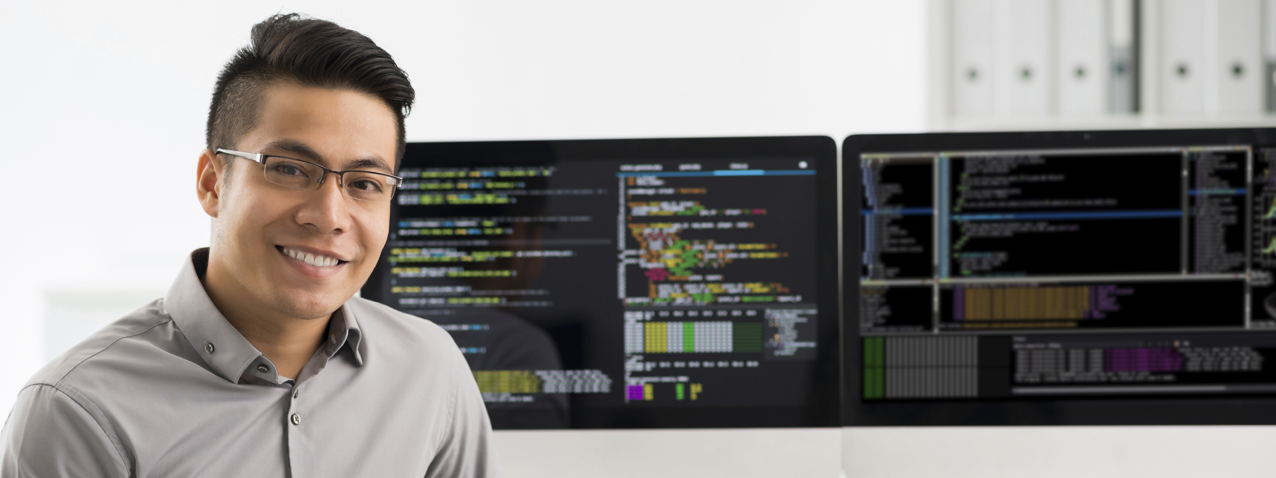 Male student looking with double monitors in the background.