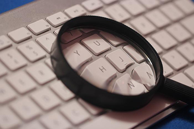 This photographic still life was composed of a black magnifying glass set atop the center of a computer keyboard.