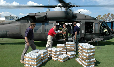 Photo: Individuals loading supplies into a helicopter.