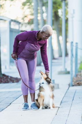 A senior woman walking with her dog