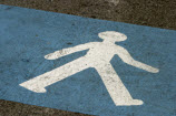 photo of walking sign on pavement near crosswalk