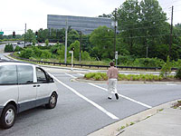 photo of man walking in crosswalk