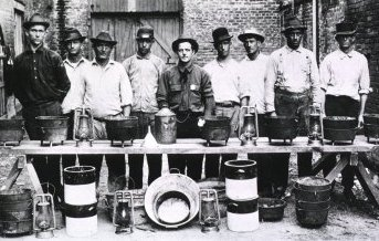 Rat Catchers in New Orleans; Group portrait of nine men standing behind a makeshift table