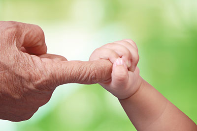 Baby grasps an adult's index finger
