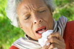 Older woman sneezing