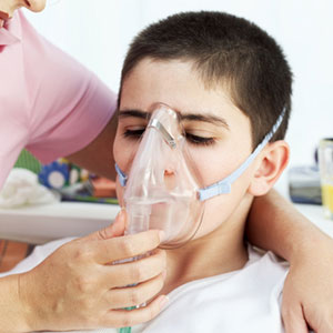 A young boy wears an oxygen mask while receiving a breathing treatment