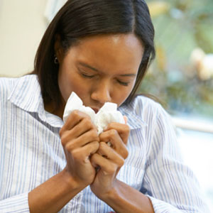 A sick young woman sneezing into a tissue