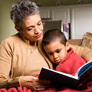A grandmother reading to her sick grandson