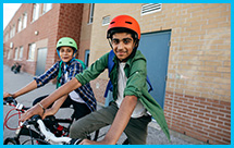 Two young boys sit on bikes outside of a school building.