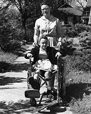 Historic photo of woman pushing child in wheelchair.