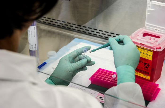 CDC scientist extracting viral RNA from samples of poliovirus genetic material for molecular testing.