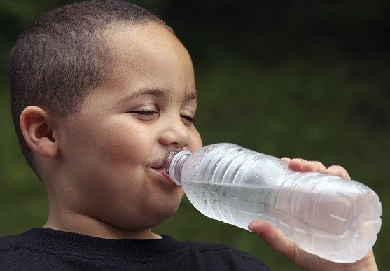 Image of a boy drinking a bottle of water