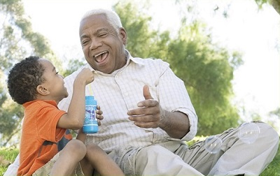 Young boy and grandfather blowing bubbles outside