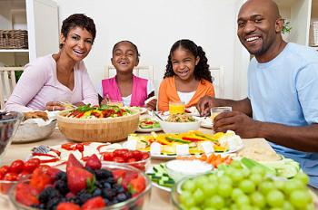 Family of four at dinner table eating healthy fruits and vegetables