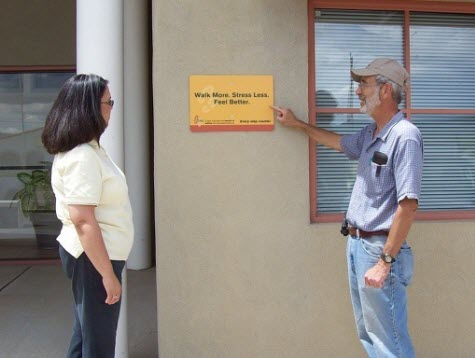 Dr. Kozoll shows Rhonda Jacquez, manager of the Cuba Credit Union, a sign on the credit union building reading,