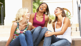 Three young women sitting on steps laughing