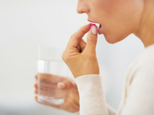 Woman taking pill with glass of water