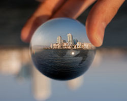 A hand holds a glass sphere with an inverted cityscape in its reflection