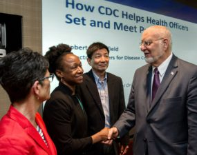 CDC Director Dr. Robert R. Redfield (right) greets public health officials.