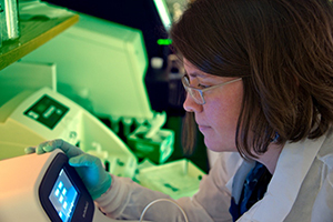 Microbiologist loading bacterial DNA into Next Generation Sequencing technology.*