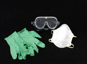 A pair of safety goggles, a dust mask, and a pair of rubber gloves on a black background