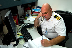 A plublic health officer on the phone and writing in a notepad.