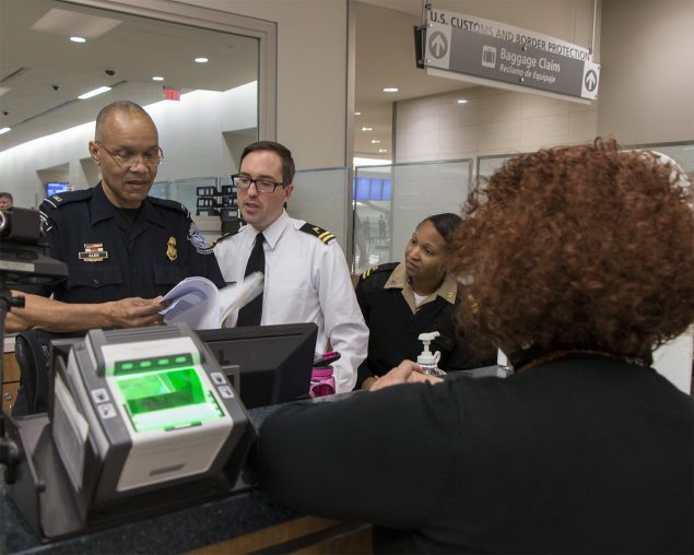 At the passport booth in an international airport, a Customs and Border Protection Officer works with two CDC Quarantine Public Health Officers to assess a sick traveler before allowing entry into the United States.
