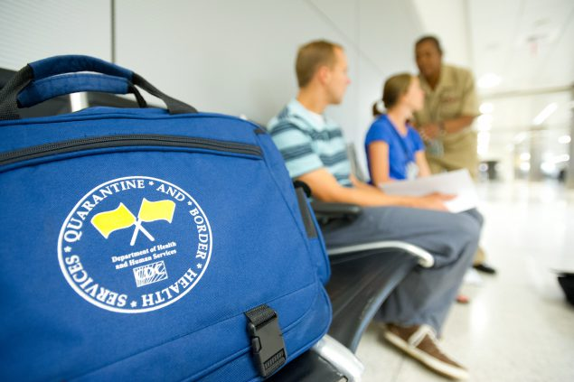 "Foreground has a blue bag with the words ""Quarantine and Border Health Services"" and yellow quarantine flags on it. Blurred in the background is a CDC Quarantine Public Health Officer assessing a sick traveler and companion at a US international airport."