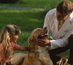 man in white lab coat with a girl looking at a dog