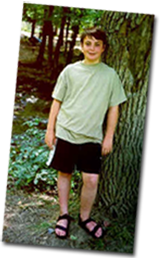 Sean leaning against a tree