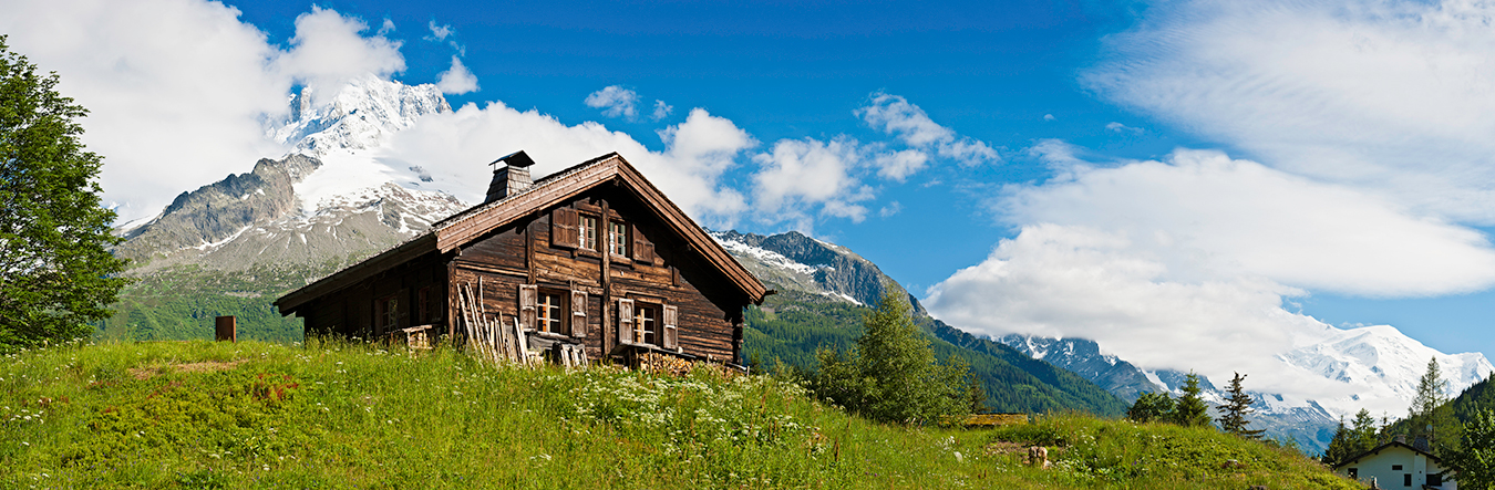 Cabin in a field with mountains in the background