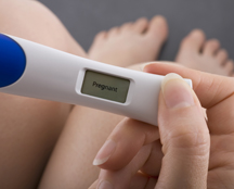 photo of a woman holding a pregnancy test, testing positive