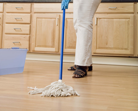 Person mopping floor with disinfectant