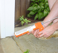 Person using caulk gun to seal holes on exterior of house