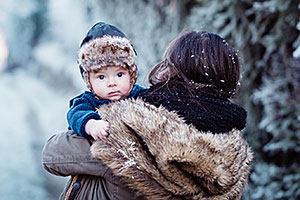 Alaska Native mother carrying her infant son outside in a wintry wonderland