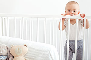 Infant standing up in crib teething on crib rail