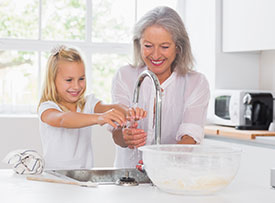 Grandmother and granddaughter washing their hands.