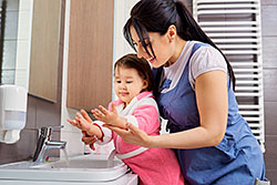Mother helping toddler wash hands