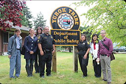 People gathered around a sign for the Yurok Tiibe Department of Public Safety